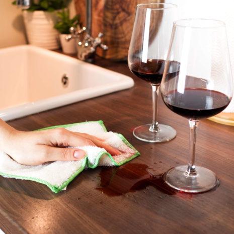 verschütteter Rotwein wird mit einem Allzwecktuch aufgewischt