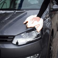 Mit einem Allzwecktuch XXL in der Hand wird der Lack eines Auto abgetrocknet